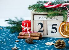 Wooden calendar with 25 December date in it on green place mat, candle, fir tree, dried oranges, pines. Christmas celebration stock image