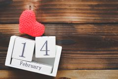 Wooden Calendar On February 14, red heart were placed side by side with old wooden background. stock photos