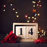 Wooden calendar from February 14 and a red rose On a dark wooden background with copy space. Valentine`s Day. Greeting card stock image