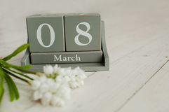 Wooden calendar with 8 March and floowers on white background Royalty Free Stock Image