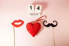 Wooden calendar and red heart with mustaches and lips paper prop on pink background. Valentine`s day concept Royalty Free Stock Photo