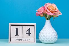 Wooden calendar, vase with flowers. February 14 on the calendar. Congratulations on Valentine`s Day royalty free stock photo