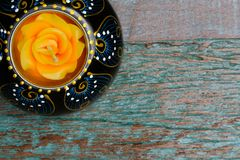 A wooden candle holder with an orange candle. A handmade oriental style wood candle holder and an orange wax candle, on a blue-green wooden table background, top royalty free stock photography