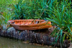 Wooden Canoe. A small wooden canoe hidden in the grass, on the river bank stock image