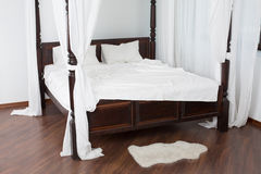 Wooden canopy bed and a white hide on the floor Stock Photos