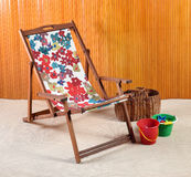 Wooden canvas beach or deck chair. Wooden canvas folding beach or deck chair with colorful floral print textile alongside plastic kids buckets and a wicker Royalty Free Stock Images
