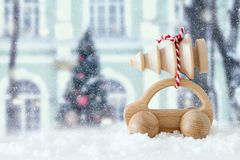 Wooden car carrying a christmas tree in front of dreamy and abstract magical winter landscape. stock photos