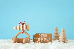 Wooden car carrying a christmas tree in front of pastel background. royalty free stock photos