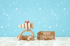 Wooden car carrying a christmas tree in front of pastel background. stock photos