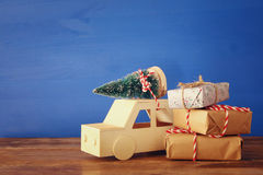 Wooden car carrying a christmas tree and gifts Royalty Free Stock Photo