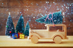 Wooden car carrying a christmas tree. Glitter overlay.  royalty free stock photo