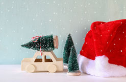 wooden car carrying a christmas tree next santa claus hat Royalty Free Stock Photography