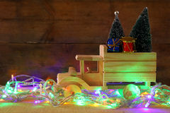 Wooden car carrying a christmas tree next to garland lights Royalty Free Stock Image