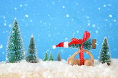 Wooden car carrying a christmas tree with santa hat in front of blue background. Wooden car carrying a christmas tree with santa hat in front of blue background stock photos