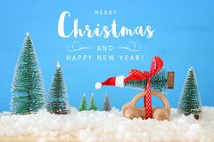 Wooden car carrying a christmas tree with santa hat in front of blue background. Wooden car carrying a christmas tree with santa hat in front of blue background royalty free stock images