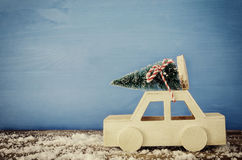 Wooden car carrying a christmas tree on snowy table Stock Photo