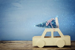 Wooden car carrying a christmas tree on wooden table Stock Photo