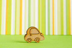 Wooden car icon on green striped background.  Royalty Free Stock Photography