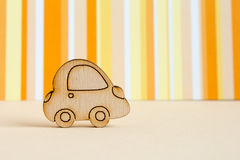 Wooden car icon on orange striped background.  royalty free stock photography