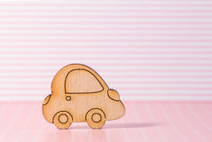 Wooden car icon on pink striped background.  royalty free stock images