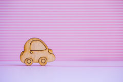 Wooden car icon on pink striped background. Concept of moving. Symbol of traveling royalty free stock photography