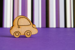 Wooden car icon on purple striped background.  stock photos