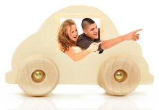 Wooden Car Toy with Couple. Natural colored wooden toy  car over white background with young couple in window Royalty Free Stock Photos