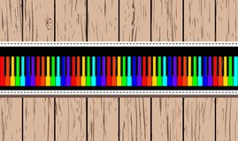 Wooden card with rainbow piano. Stock Photos