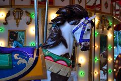 Wooden Carousel Horse Detail. An old carousel lit up at dusk. Close-up of a colorful wooden horse on a carousel Royalty Free Stock Images