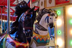 Wooden Carousel Horsse Detail. An old carousel lit up at dusk. Close-up of two colorful wooden horses on a carousel Royalty Free Stock Image