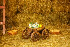 Wooden cart with flowers and fruits in a barn with hay royalty free stock image