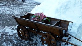 Wooden cart on a snowy stone pavement. Wooden cart with decorative grapes and keg of wine on a snowy stone pavement, winter season Royalty Free Stock Images