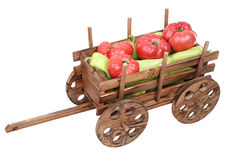 Wooden cart with vegetables. Wooden decorative cart filled with vegetables - tomatoes and pepper isolated on white with clipping path Stock Images
