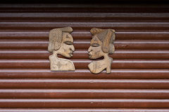 Wooden Carved African Faces. On Wooden Wall Royalty Free Stock Photography