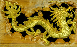 The wooden carved Chinese dragon. On black background Royalty Free Stock Photography