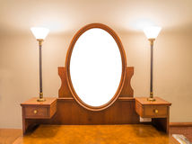 Wooden carved dressing table with blank frame in room Stock Images