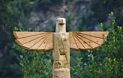 Wooden carved eagle on top of totem pole. Wooden carved eagle on top of huge totem pole Royalty Free Stock Photo