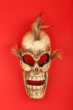 Wooden carved skull death mask on red Royalty Free Stock Image