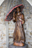 Wooden carved statue of Jesus holding an umbrella Royalty Free Stock Photography