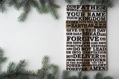Wooden carved word of the Lord`s Prayer on white wooden plank with fir tree branches background stock photo