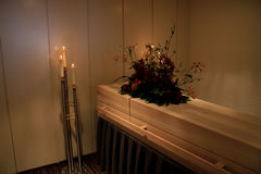Wooden casket in funeral home Stock Photo