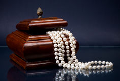 Wooden casket and pearl beads on blue Stock Photo