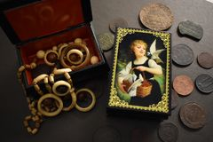 Wooden casket with women`s jewelry and old coins on a black background. royalty free stock photo