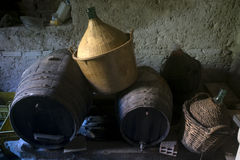 Wooden casks and demijohn in an old cellar. Old wooden barrels and wicker demijohn in an antique cellar with tuff walls Royalty Free Stock Photography
