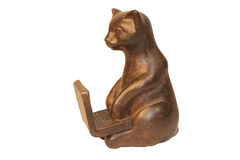 Wooden cat sits at a laptop. On a transparent background Royalty Free Stock Photography