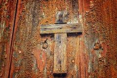 Wooden Catholic cross. A brownish wooden Catholic cross nailed on grungy orange old wall Royalty Free Stock Image