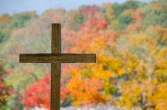 Wooden cemetery cross and fall color trees Stock Images