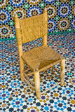 Wooden chair. On brightly colored Moroccan palace floor tiles royalty free stock images