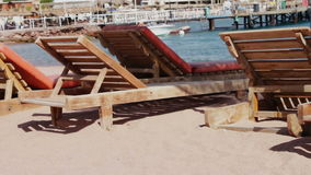 Wooden chair at the beach of background of blue sea. Empty wooden deck chairs on the beach on the background of blue sea stock video footage