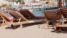 Wooden chair at the beach of background of blue sea. Empty wooden deck chairs on the beach on the background of blue sea stock video